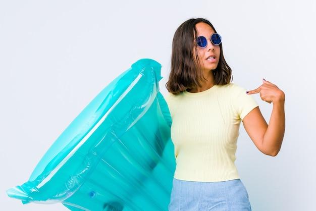 Giovane donna di razza mista che tiene in mano una persona con materasso ad aria che indica a mano uno spazio per la copia di una maglietta, orgogliosa e fiduciosa