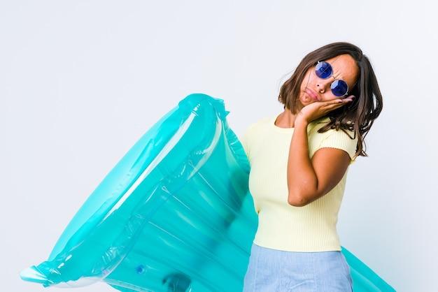Giovane donna di razza mista che tiene un materasso ad aria che sbadiglia mostrando un gesto stanco che copre la bocca con la mano.
