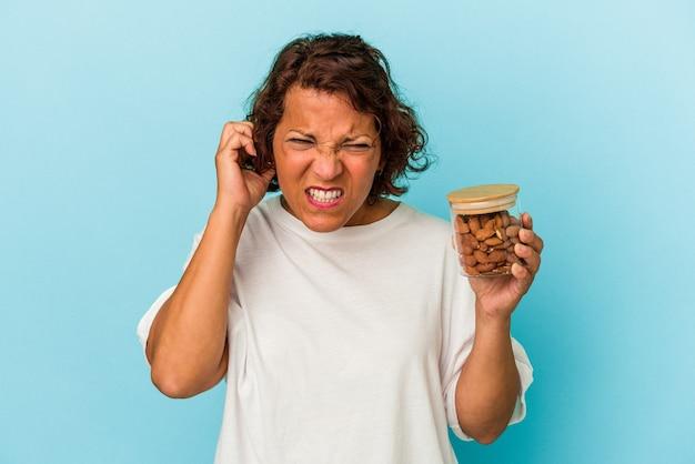 Giovane donna di razza mista che tiene un barattolo di mandorle isolato su sfondo blu che copre le orecchie con le mani.
