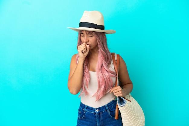 La giovane donna di razza mista che tiene una borsa da spiaggia con pamela isolata su sfondo blu soffre di tosse e si sente male