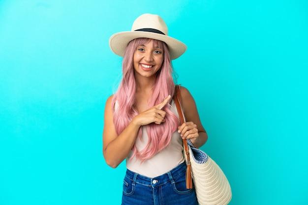 Giovane donna di razza mista che tiene una borsa da spiaggia con pamela isolata su sfondo blu che punta di lato per presentare un prodotto
