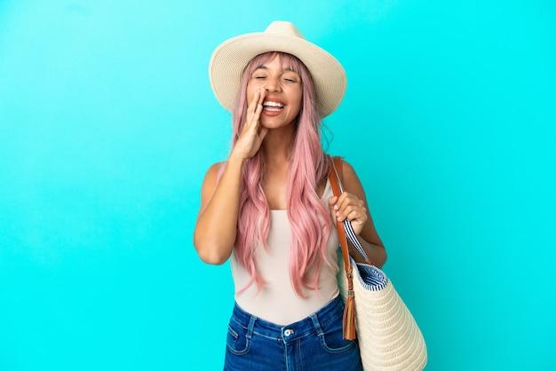 Giovane donna di razza mista che tiene una borsa da spiaggia con pamela isolata su sfondo blu che grida e annuncia qualcosa
