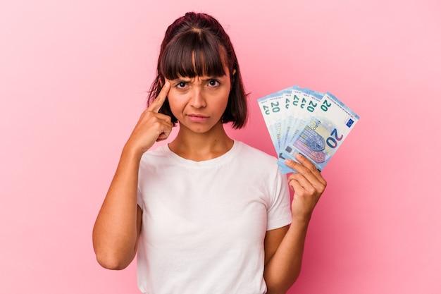 Giovane donna di razza mista che tiene banconote isolate su sfondo rosa che punta il tempio con il dito, pensando, concentrato su un compito.