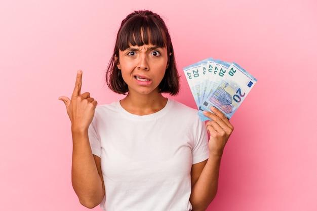 Giovane donna di razza mista che tiene banconote isolate su sfondo rosa che mostra un gesto di delusione con l'indice.