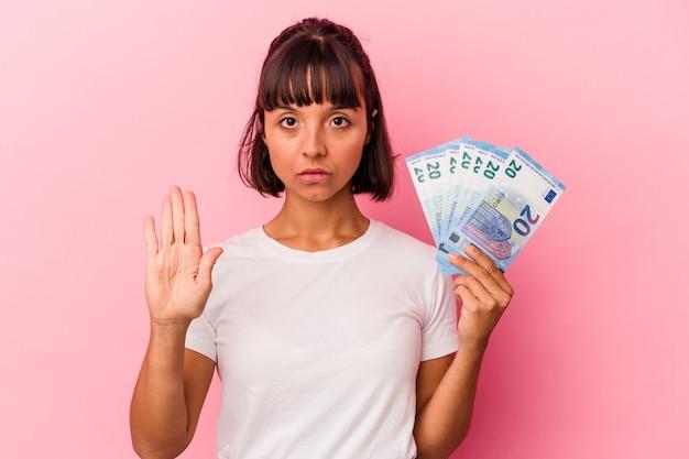 Giovane donna di razza mista che tiene banconote isolate su sfondo rosa in piedi con la mano tesa che mostra il segnale di stop, impedendoti.