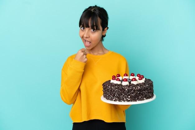 Giovane donna di razza mista che tiene la torta di compleanno che celebra una vittoria
