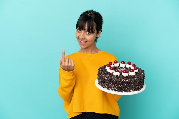 Giovane donna della corsa mista che tiene la torta di compleanno che fa il gesto venente