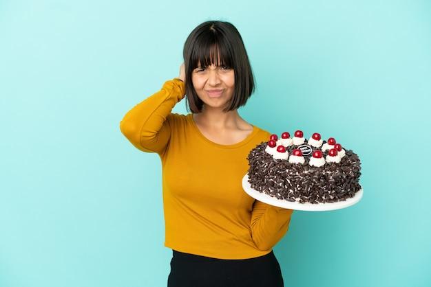 Giovane donna di razza mista che tiene la torta di compleanno frustrata e copre le orecchie