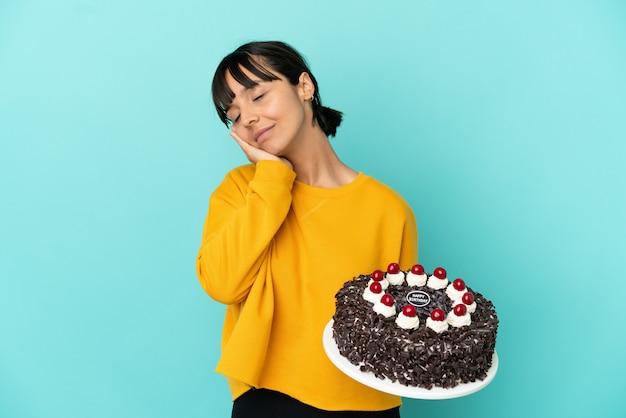 Giovane donna di razza mista che tiene la torta di compleanno che fa il gesto del sonno in un'espressione adorabile