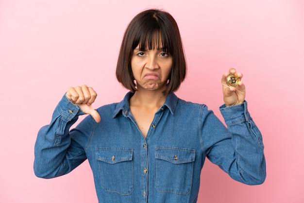 Giovane donna di razza mista che tiene in mano uno sfondo isolato bitcoin che mostra il pollice verso il basso con espressione negativa