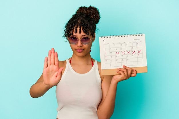 Giovane donna di razza mista che tiene il calendario isolato su sfondo blu in piedi con la mano tesa che mostra il segnale di stop, impedendoti.