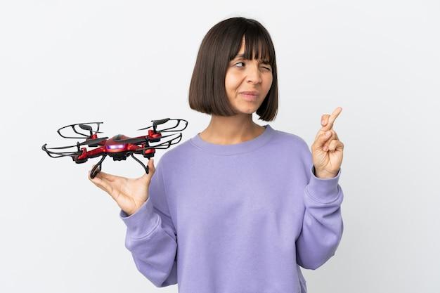 Giovane donna di razza mista che tiene in mano un drone isolato su sfondo bianco con le dita incrociate e augurando il meglio