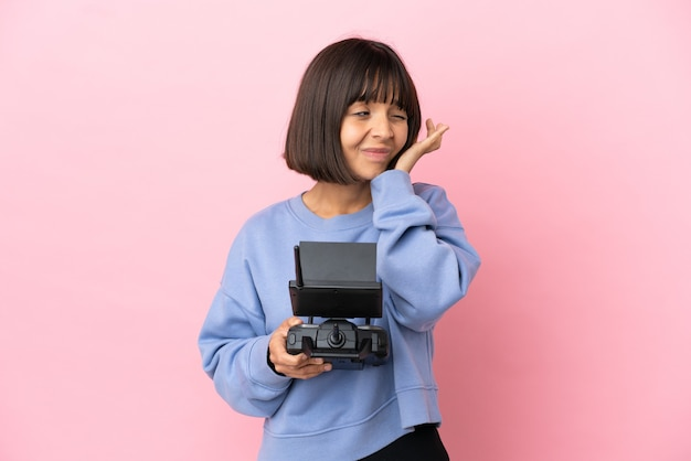 Giovane donna di razza mista in possesso di un telecomando drone isolato su sfondo rosa frustrata e che copre le orecchie