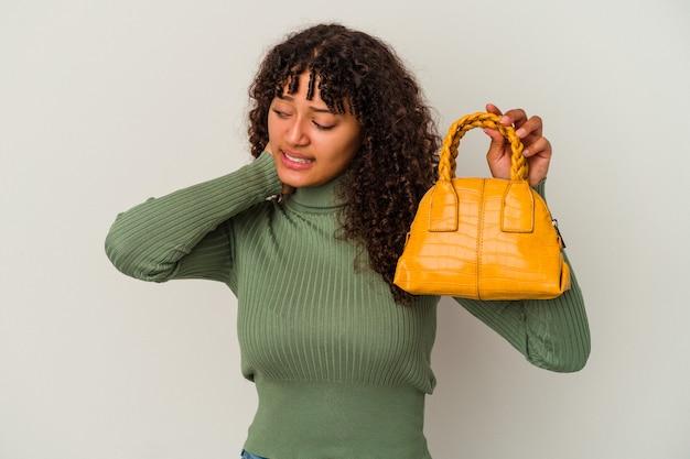 Giovane donna di razza mista che tiene una borsetta isolata su sfondo bianco toccando la parte posteriore della testa, pensando e facendo una scelta.