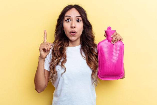 Giovane donna di razza mista che tiene una borsa calda isolata su sfondo giallo con qualche grande idea, concetto di creatività.