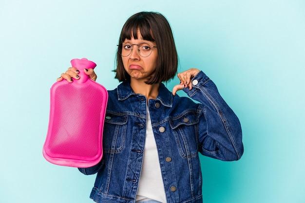 La giovane donna di razza mista che tiene una bottiglia d'acqua calda isolata su sfondo blu si sente orgogliosa e sicura di sé, esempio da seguire.