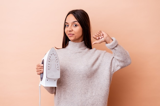 La giovane donna di razza mista che tiene un ferro da stiro isolato si sente orgogliosa e sicura di sé, esempio da seguire.