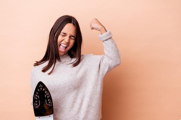 Giovane donna di razza mista che tiene un pugno di sollevamento isolato di ferro dopo una vittoria, concetto di vincitore.