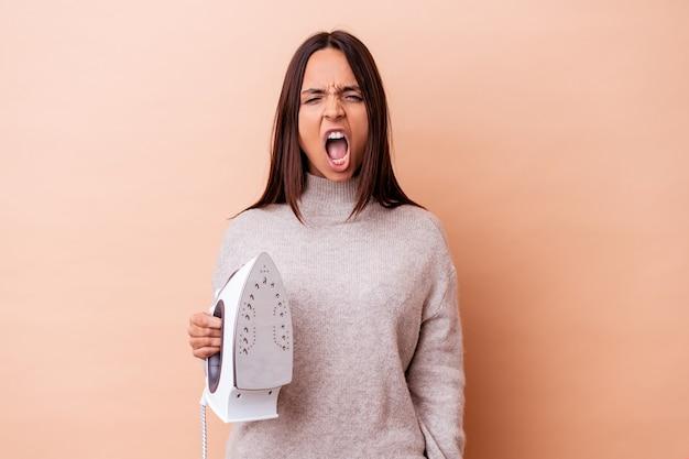 Giovane donna di razza mista che tiene un ferro isolato urlando molto arrabbiato e aggressivo.