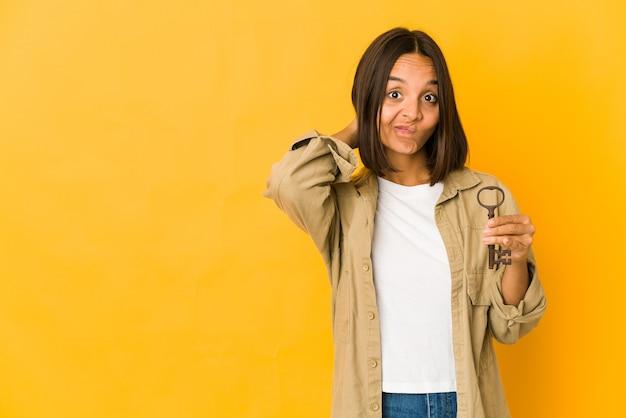 Giovane donna di razza mista che tiene una chiave