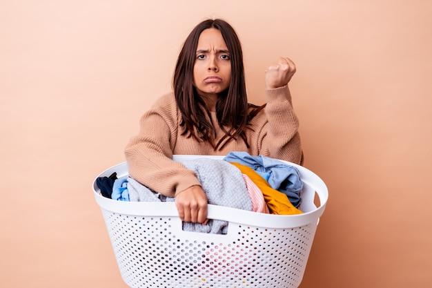 Giovane donna di razza mista che tiene una lavanderia isolata che mostra il pugno alla macchina fotografica, espressione facciale aggressiva.