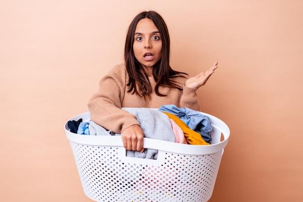 Giovane donna di razza mista in possesso di un bucato isolato sorpreso e scioccato.