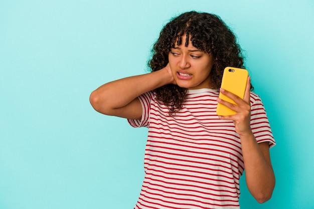 Giovane donna di razza mista in possesso di un telefono cellulare isolato su sfondo blu, toccando la parte posteriore della testa, pensando e facendo una scelta.