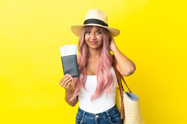 Giovane donna di razza mista con passaporto e borsa da spiaggia isolata su sfondo giallo con dubbi