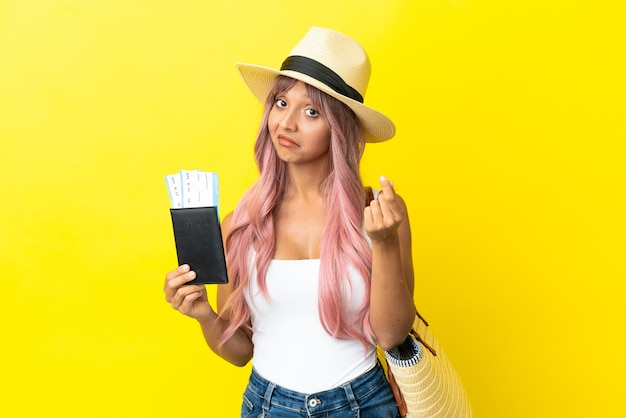 Giovane donna di razza mista con passaporto e borsa da spiaggia isolata su sfondo giallo che fa gesti di denaro