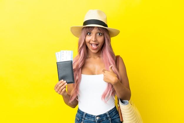 Giovane donna di razza mista con passaporto e borsa da spiaggia isolata su sfondo giallo con espressione facciale a sorpresa