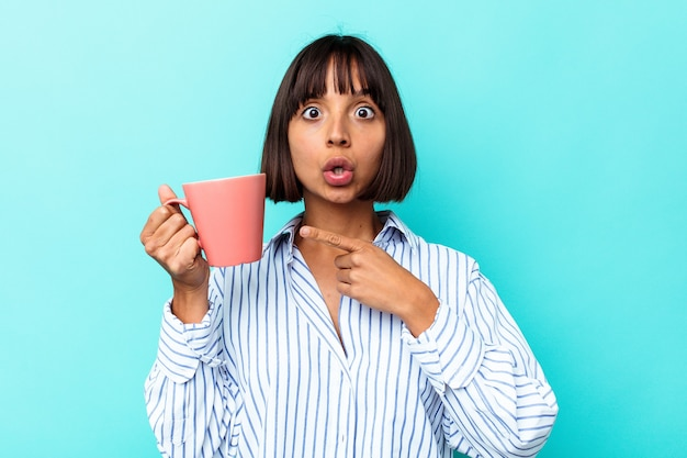 Giovane donna di razza mista che tiene una tazza rosa isolata su sfondo blu che punta al lato