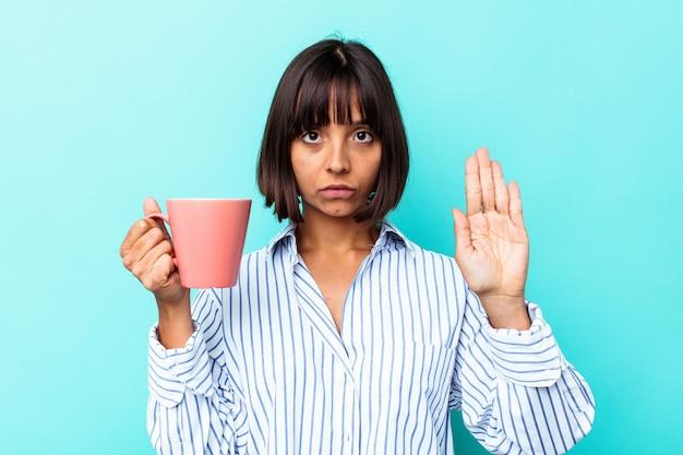 Giovane donna di razza mista che tiene una tazza rosa isolata su sfondo blu in piedi con la mano tesa che mostra il segnale di stop, impedendoti.