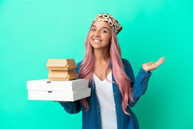Giovane donna di razza mista che tiene pizze e hamburger isolati su sfondo verde estendendo le mani di lato per invitare a venire