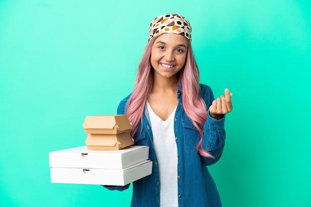 Giovane donna di razza mista che tiene pizze e hamburger isolati su sfondo verde che fa gesti di denaro