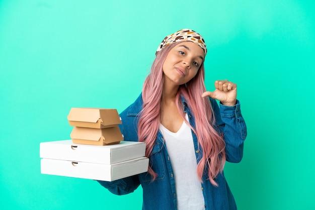 Giovane donna di razza mista che tiene pizze e hamburger isolati su sfondo verde orgogliosa e soddisfatta di sé