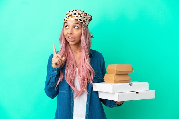 Giovane donna di razza mista che tiene pizze e hamburger isolati su sfondo verde pensando a un'idea che punta il dito verso l'alto