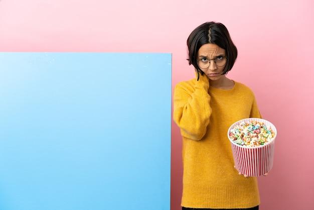 Giovane donna di razza mista che tiene i popcorn con un grande striscione su sfondo isolato frustrata e che copre le orecchie