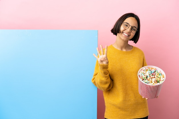 Giovane donna di razza mista che tiene i popcorn con un grande striscione su sfondo isolato felice e contando quattro con le dita