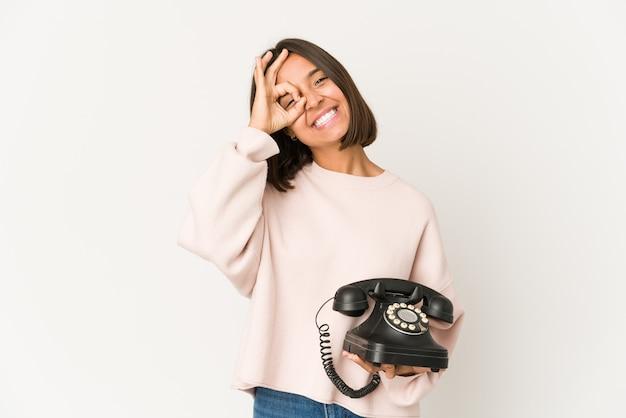 Giovane donna di razza mista che tiene un telefono