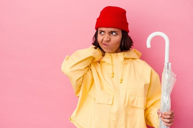 Giovane donna di razza mista che tiene un ombrello isolato sulla parete rosa che tocca la parte posteriore della testa, pensando e facendo una scelta