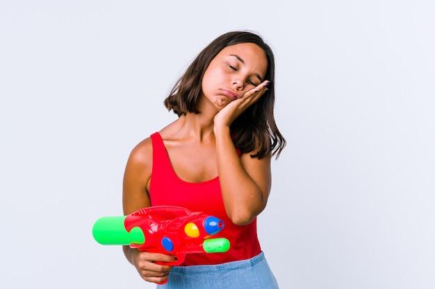 Giovane donna di razza mista che tiene una pistola ad acqua isolata che è annoiata, affaticata e ha bisogno di una giornata di relax.
