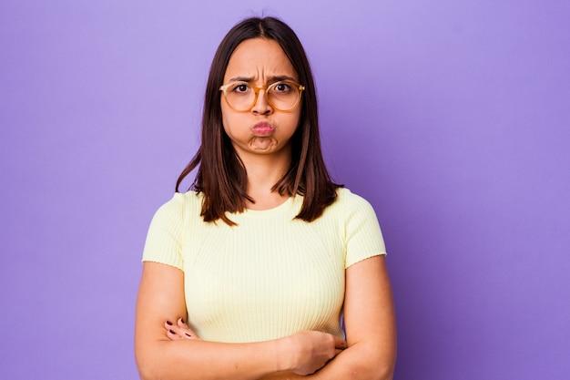 La giovane donna di razza mista isolata soffia sulle guance, ha un'espressione stanca. concetto di espressione facciale.