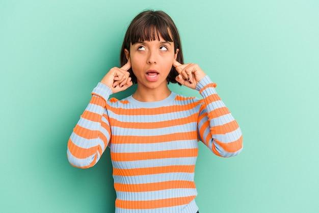 Giovane donna di razza mista isolata su sfondo blu che copre le orecchie con le dita, stressata e disperata da un ambiente rumoroso.