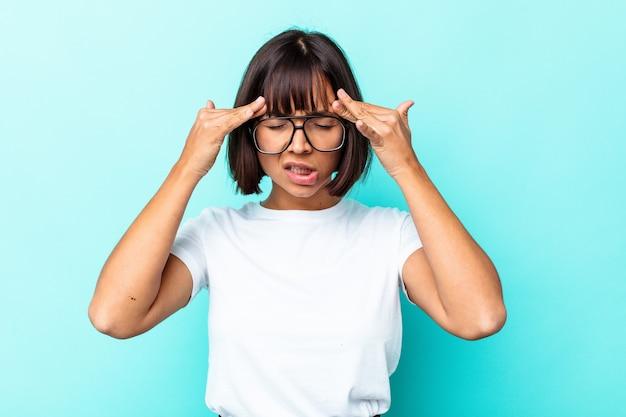 Giovane donna di razza mista isolata su sfondo blu con mal di testa, toccando la parte anteriore del viso.