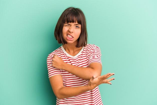 Giovane donna di razza mista isolata su sfondo blu che ha un dolore alla spalla.