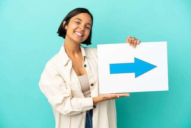 Giovane donna di razza mista isolata su sfondo blu in possesso di un cartello con il simbolo della freccia con felice espressione