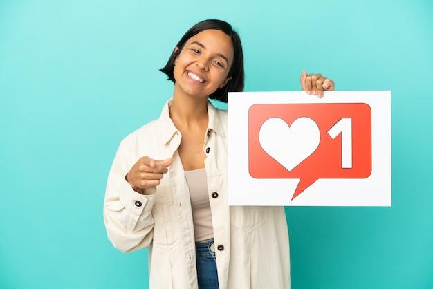 Giovane donna di razza mista isolata su sfondo blu che tiene in mano un cartello con l'icona mi piace e che punta verso la parte anteriore