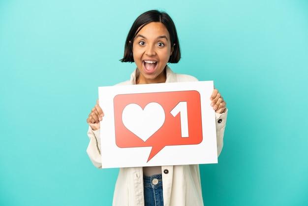 Giovane donna di razza mista isolata su sfondo blu che tiene un cartello con l'icona mi piace con espressione felice happy