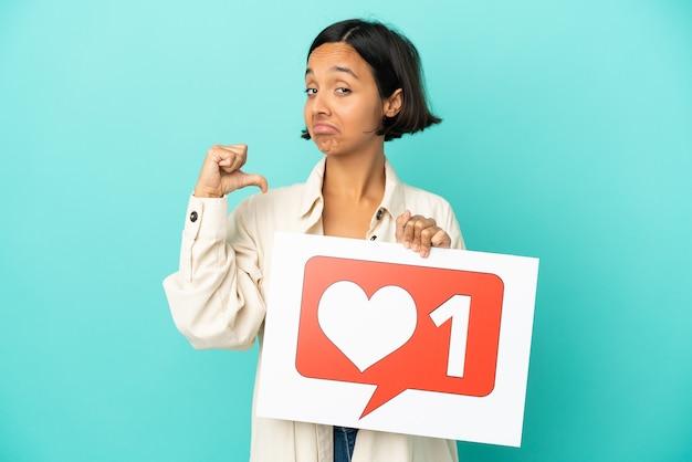 Giovane donna di razza mista isolata su sfondo blu che tiene un cartello con l'icona mi piace con gesto orgoglioso