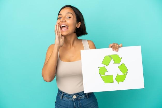 Giovane donna di razza mista isolata su sfondo blu con in mano un cartello con l'icona di riciclo e urlando